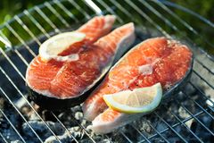 Salmon on grill. Salmon preparation process on wooden grill. Grilled fish steaks on fire. Top view stock photos