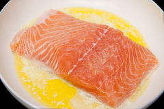 Salmon. Preparing with butter in the frying pan Royalty Free Stock Images