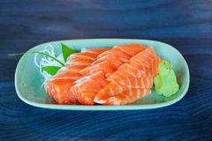 Salmon raw sashimi on green Japanese traditional dish on black t Stock Photos