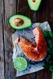 Salmon. Raw salmon steak, avocado, lime and parsley on rustic wooden board - healthy food, diet or cooking concept. Top view Royalty Free Stock Image