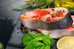 Salmon. Raw trout fish steak with herbs and lemon on black slate background. Cooking royalty free stock photography
