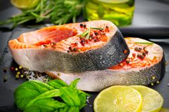 Salmon. Raw trout fish steak with herbs and lemon on black slate background. Cooking, seafood stock photo