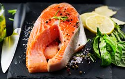 Salmon. Raw trout fish steak with herbs and lemon on black slate background. Cooking, seafood. Healthy eating stock photography