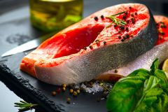 Salmon. Raw trout fish steak with herbs and lemon on black slate background. Cooking, seafood. Healthy eating stock photo