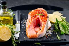 Salmon. Raw trout fish steak with herbs and lemon on black slate background. Cooking, seafood stock photography