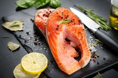 Salmon. Raw trout fish steak with herbs and lemon on black slate background. Cooking, seafood. Healthy eating. Concept stock image