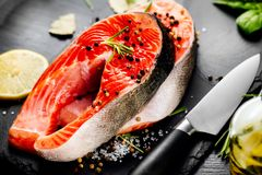 Salmon. Raw trout fish steak with herbs and lemon on black slate background. Cooking, seafood Royalty Free Stock Image