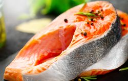 Salmon. Raw trout fish steak with herbs and lemon on black slate background. Cooking royalty free stock images