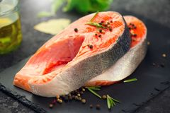 Salmon. Raw trout fish steak with herbs and lemon on black slate background. Cooking royalty free stock photos