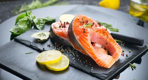 Salmon. Raw trout fish steak with herbs and lemon on black slate background. Cooking stock photo