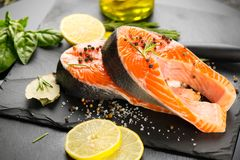 Salmon. Raw trout fish steak with herbs and lemon on black slate background. Cooking royalty free stock photo