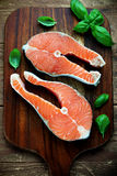 Salmon raw. Two pieces of red salmon fillets placed on the wooden cutting board Royalty Free Stock Images