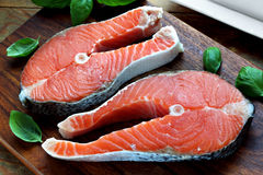 Salmon raw. Two pieces of red salmon fillets placed on the wooden cutting board Stock Photo