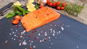 Salmon of red color. Salted salmon fillet with spices. Raw salmon filet on dark slate background, wild atlantic fish. Fresh fish. Salmon fillet on black stock image