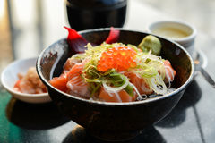 Salmon Rice. In a black bowl served with soup and kimji Stock Photo