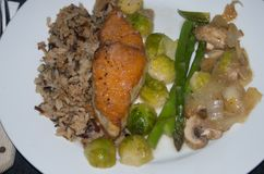 Salmon, rice, Brussel sprouts, asparagus, onions and mushrooms. royalty free stock photo