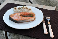 Salmon and rice. Fillet of salmon on a white plate with rice. Simple decoration Stock Images