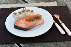Salmon and rice. Fillet of salmon on a white plate with rice. Simple decoration Royalty Free Stock Photos