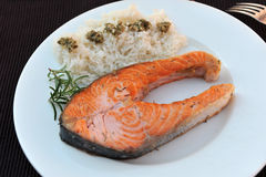 Salmon and rice. Fillet of salmon on a white plate with rice. Simple decoration Royalty Free Stock Photo