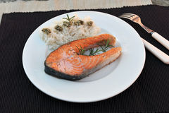 Salmon and rice. Fillet of salmon on a white plate with rice. Simple decoration Royalty Free Stock Image