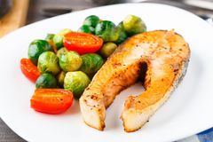 Salmon with roasted brussels sprout and tomato Royalty Free Stock Photos