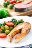 Salmon with roasted brussels sprout and tomato Stock Photography