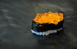 Salmon Roe eller Ikura sushi med svart bakgrund Arkivfoton