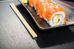 Salmon roll with chopsticks. For restaurant menu Royalty Free Stock Photography