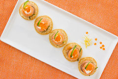 "Salmon rolls with cheese, caviar and cucumber. Red salmon rolls with chees, caviar and cucumber on"" blinis"" base, on orange background Stock Images"