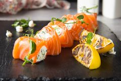 Salmon rolls stuffed with cream cheese and herbs, beautiful snack, elegant food for menu stock images