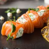 Salmon rolls stuffed with cream cheese and herbs, beautiful snack, elegant food for menu stock image