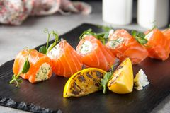 Salmon rolls stuffed with cream cheese and herbs, beautiful snack, elegant food for menu royalty free stock photos