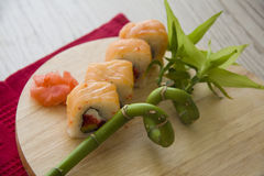 Salmon rolls on wooden background Stock Photography
