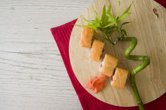Salmon rolls on wooden background Royalty Free Stock Photo