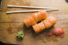 Salmon rolls on wooden board. Salmon rolls on wooden desk with wasabi stock images
