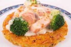 Salmon Rosti met gekookte broccoli en witte bechamelsaus die wordt gediend Stock Foto's