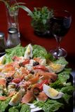 Salmon salad. Delicious salmon salad with glass of red wine on a restaurant table Stock Photography