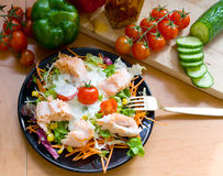 Salmon on salad. A fresh salad with fried salmon and yogurt dressing on a black dish stock photo