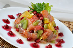Salmon salad with fruit. Salad with salmon of different fruits and pomegranate Stock Image