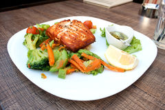 Salmon salad on a plate. A white plate with a healthy portion of salmon and salad Royalty Free Stock Images