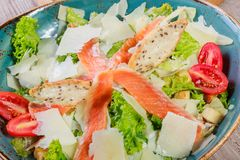 Salmon salad with tuna sauce, parmesan cheese, croutons, tomatoes, mixed greens, lettuce and glass of wine on wooden background. Mediterranean food Stock Photos