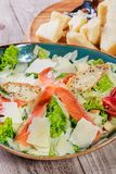 Salmon salad with tuna sauce, parmesan cheese, croutons, tomatoes, mixed greens, lettuce and glass of wine on wooden background. Mediterranean food Royalty Free Stock Photography