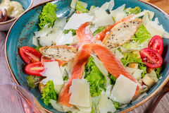 Salmon salad with tuna sauce, parmesan cheese, croutons, tomatoes, mixed greens on wooden background. Mediterranean food Stock Photography