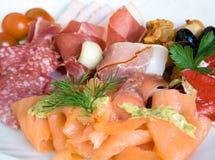 Salmon and salami salad. Close up of appetizing cold salad with salmon and salami stock image