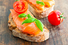 Salmon sandwich on wooden table with tomato Royalty Free Stock Image