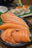 Salmon Sashimi över is på den svarta bunken Fotografering för Bildbyråer