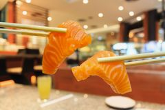 Salmon sashimi in chopsticks Stock Image