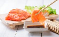 Salmon sashimi with chopsticks. Salmon sashimi set with chopsticks holding a piece of sliced salmon, healthy food and diet stock image