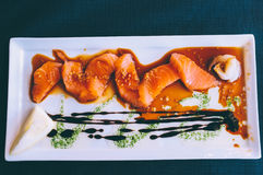 Salmon sashimi. Delicious salmon sashimi dish with sesame, soy, lemon vinaigrette on a rectangular plate Royalty Free Stock Image