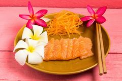 Salmon sashimi on dish with flower on wood color pink.  royalty free stock image